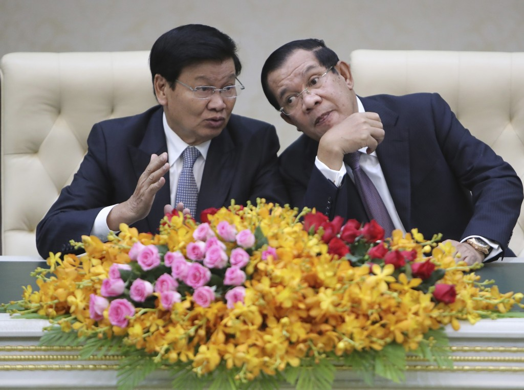 Cambodian Prime Minister Hun Sen, right, talks with his Laos counterpart Thonloun Sisoulith, left, as they witness to a signing ceremony in Phnom Penh...