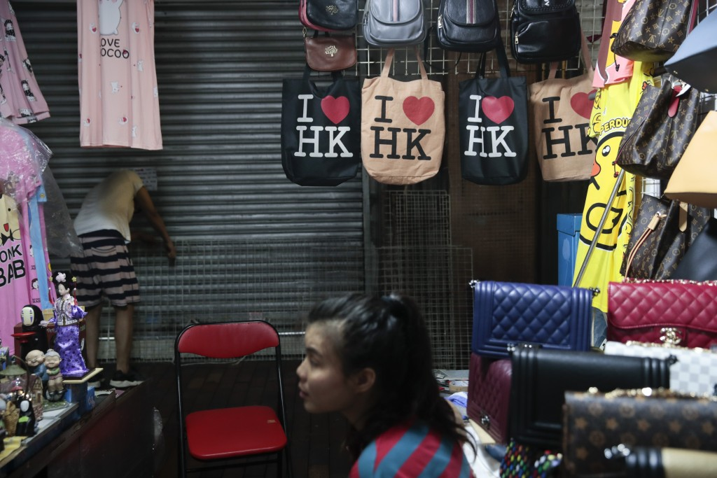 "In this Sept. 2, 2019, photo, a vendor selling handbags along with a few ""I heart HK"" tote bags, sits in her booth at Temple Street Night Market in Ho..."