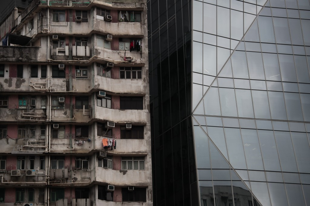In this Sept. 1, 2019, photo, an old apartment building stands next to a gleaming tower in Hong Kong. Life is not quite normal after three months of s...