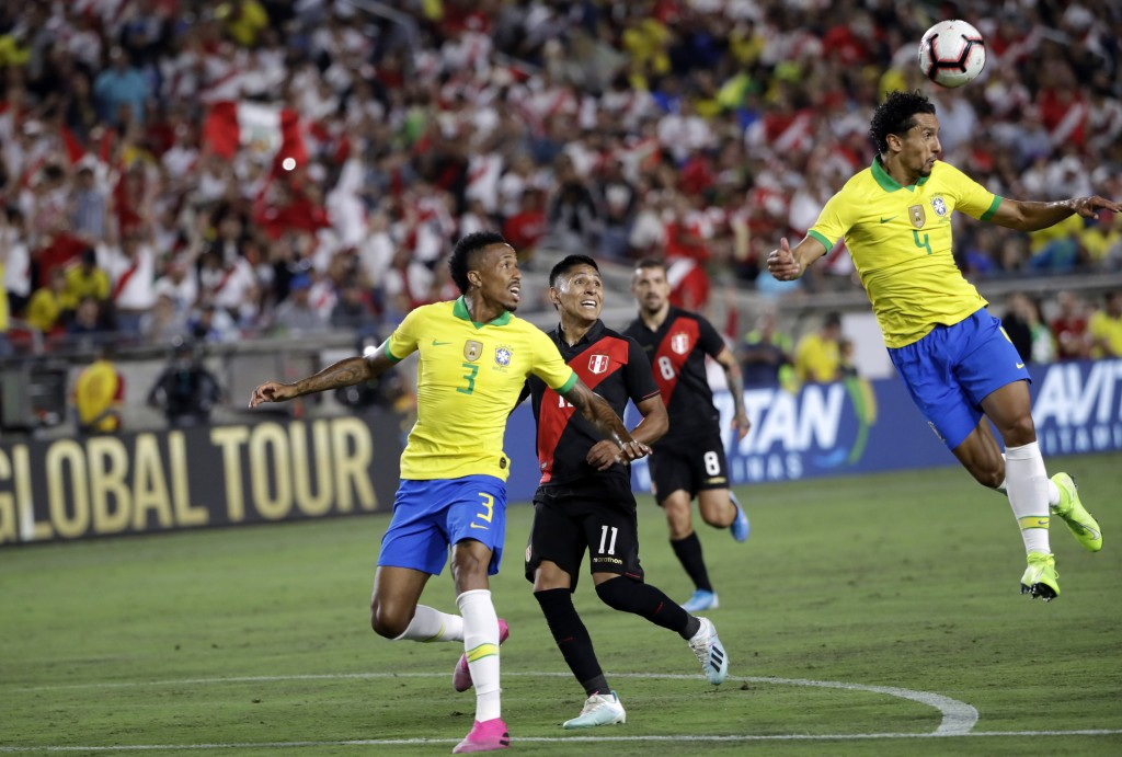 Brazil's Marquinhos, right, clears the ball with a header in front of Peru's Raul Ruidiaz (11) and Brazil's Eder Militao during the first half of an i...