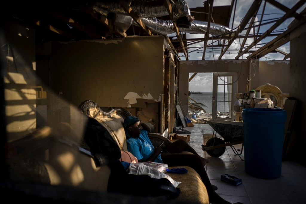 Ebony Thomas looks at her phone a she sits on a sofa inside her shattered home, in the aftermath of Hurricane Dorian, in Mclean's Town, Grand Bahama, ...