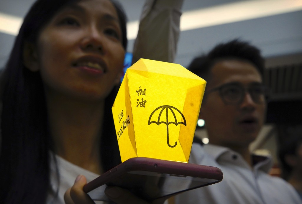 A woman holds a paper lantern over the light on her smartphone during a demonstration at the Times Square shopping mall in Hong Kong, Thursday, Sept. ...