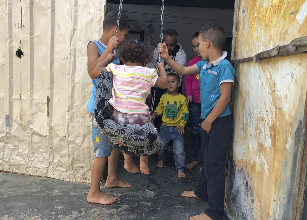 In this August 29, 2019 photo, Yousef Samara, a 42-year-old refugee from Syria's Deraa province plays with his children and nephews inside his caravan
