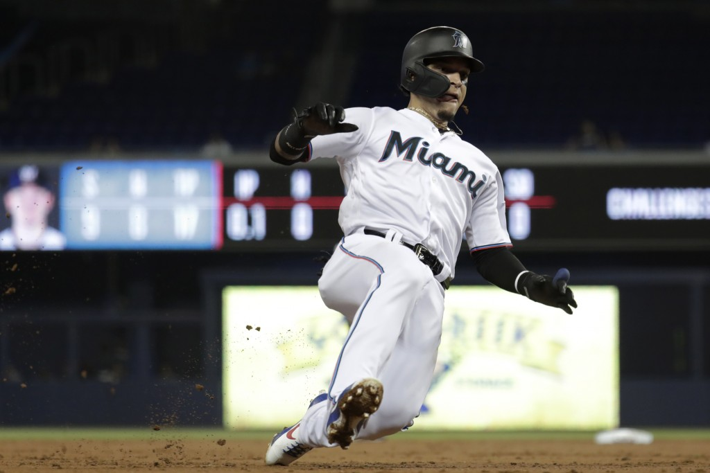 Miami Marlins' Isan Diaz slides safely into third, advancing on a single by Garrett Cooper during the first inning of the team's baseball game against...