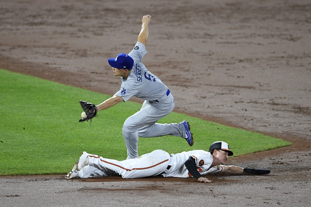 Baltimore Orioles' Austin Hays, bottom, slides toward second, advancing on a wild pitch as Los Angeles Dodgers shortstop Corey Seager (5) reaches for ...