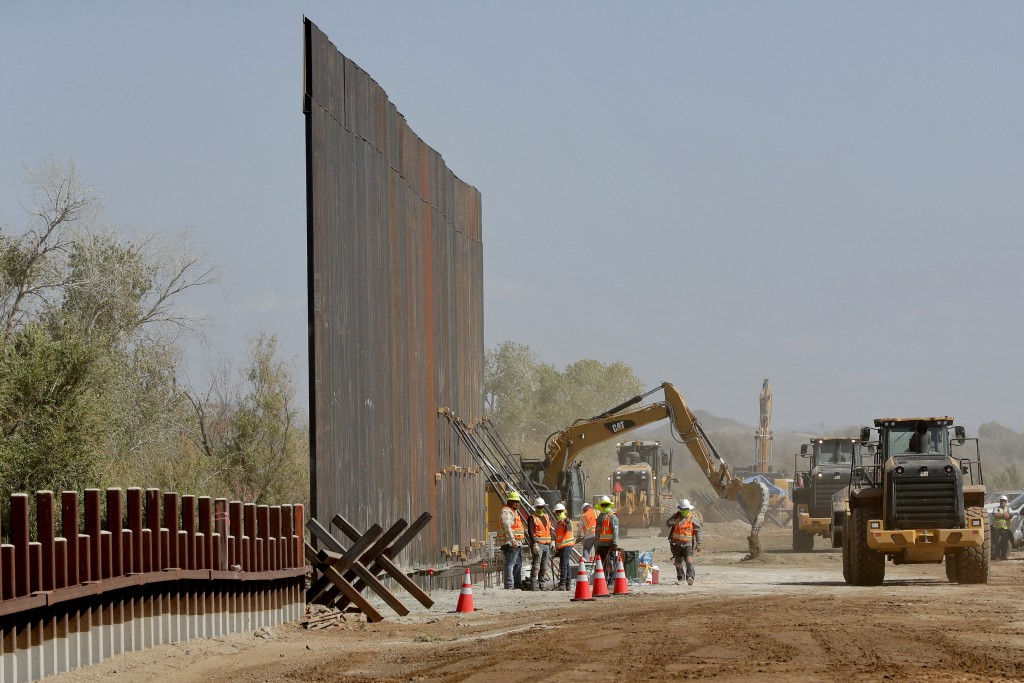 Government contractors erect a section of Pentagon-funded border wall along the Colorado River, Tuesday, Sept. 10, 2019 in Yuma, Ariz. The 30-foot hig