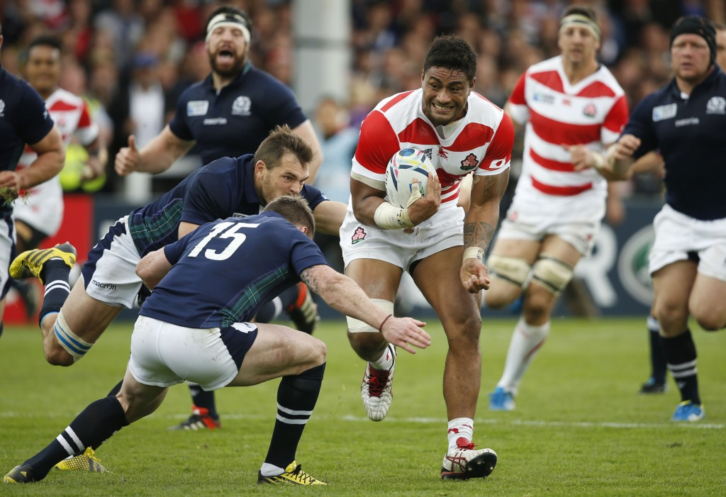 FILE - In this Wednesday, Sept. 23, 2015 file photo, Japan's Amanaki Mafi runs with the ball through Scotland's defence during the Rugby World Cup Poo