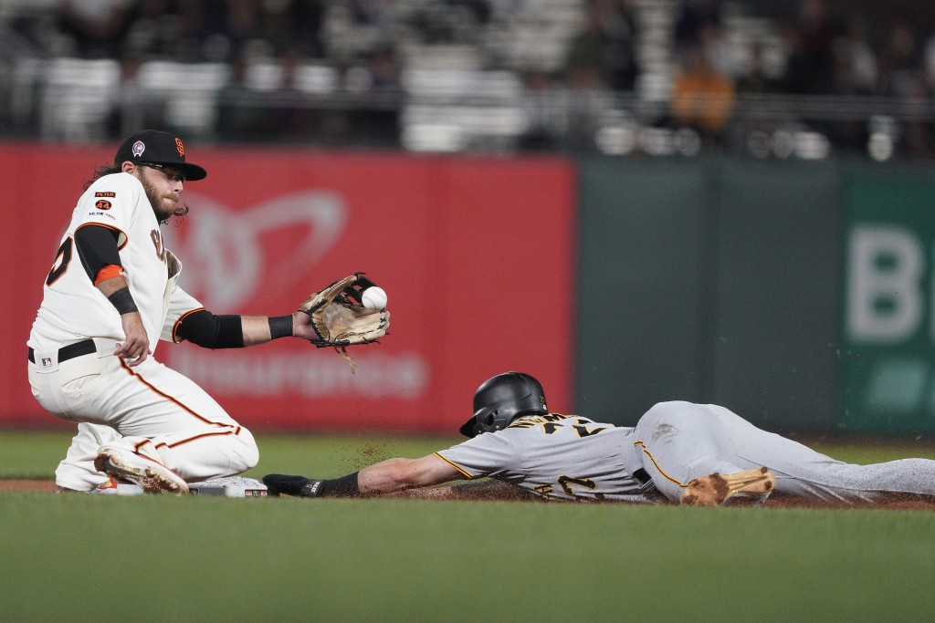 Pittsburgh Pirates' Kevin Newman, right, slides safely into second with a stolen base, next to San Francisco Giants shortstop Brandon Crawford during ...