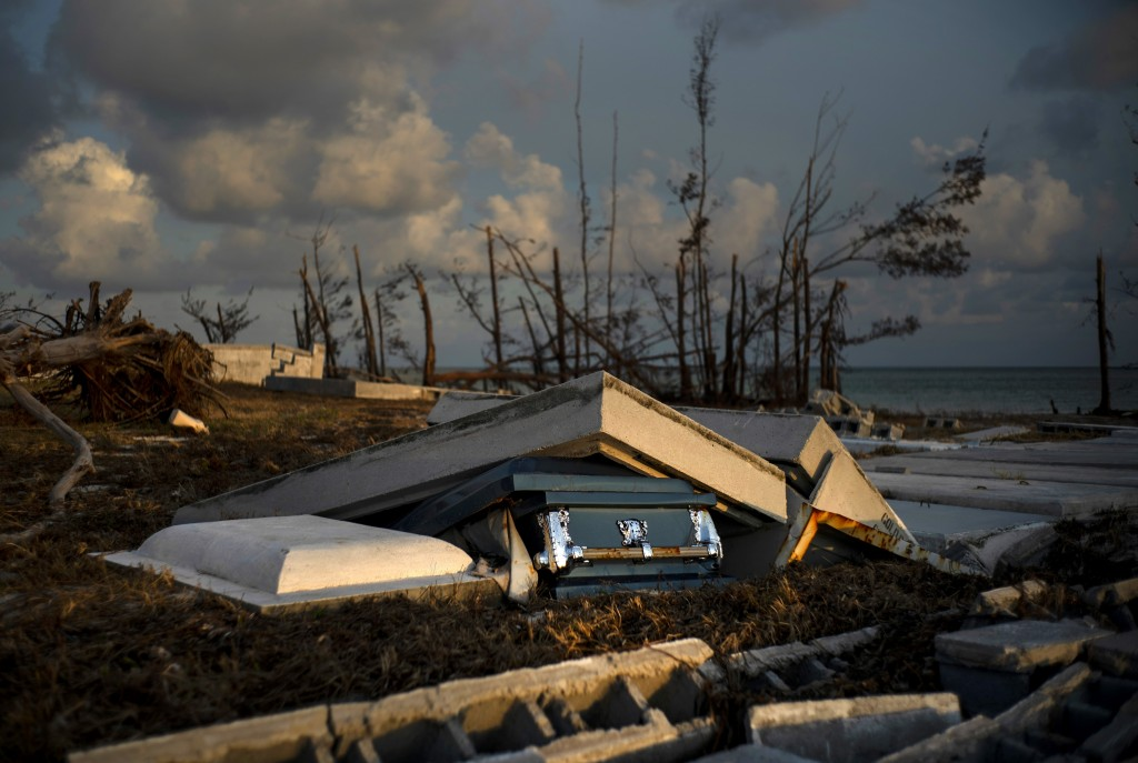 A coffin peaks out of a grave, in aftermath of Hurricane Dorian, at the shattered cemetery in Mclean's Town, Grand Bahama, Bahamas, Wednesday Sept. 11...