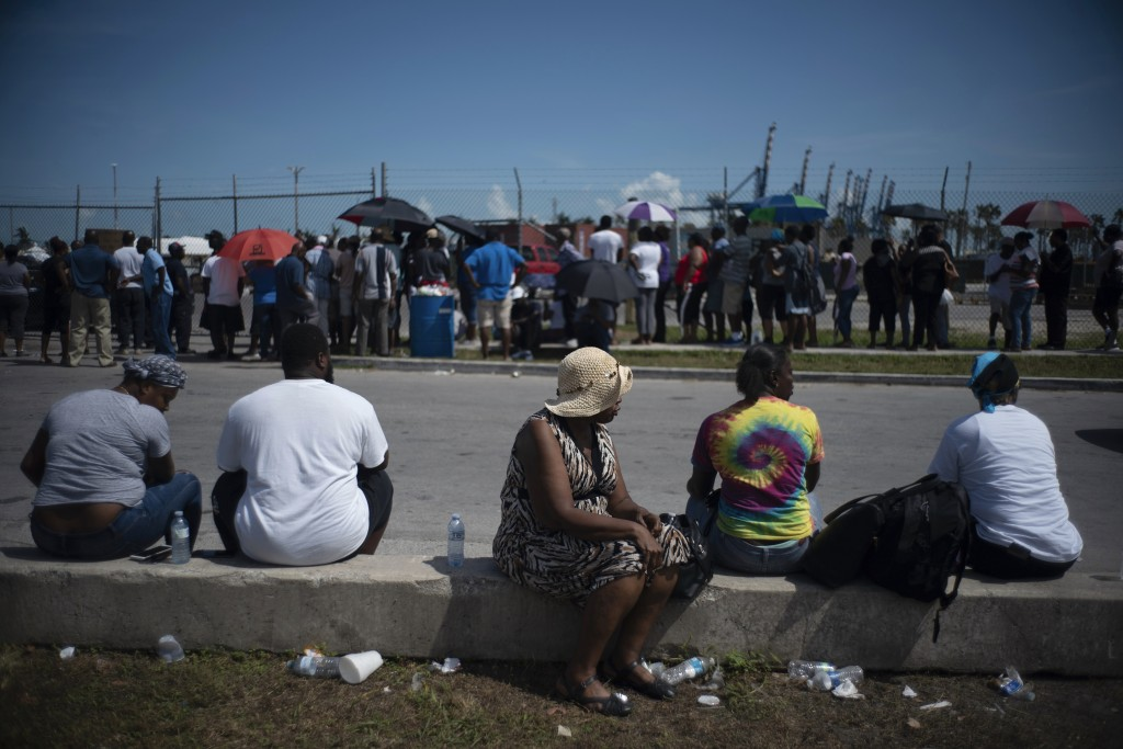 People gather at the port for aid sent by family members and friends in the aftermath of Hurricane Dorian in Freeport, Bahamas, Tuesday, Sept. 10, 201...