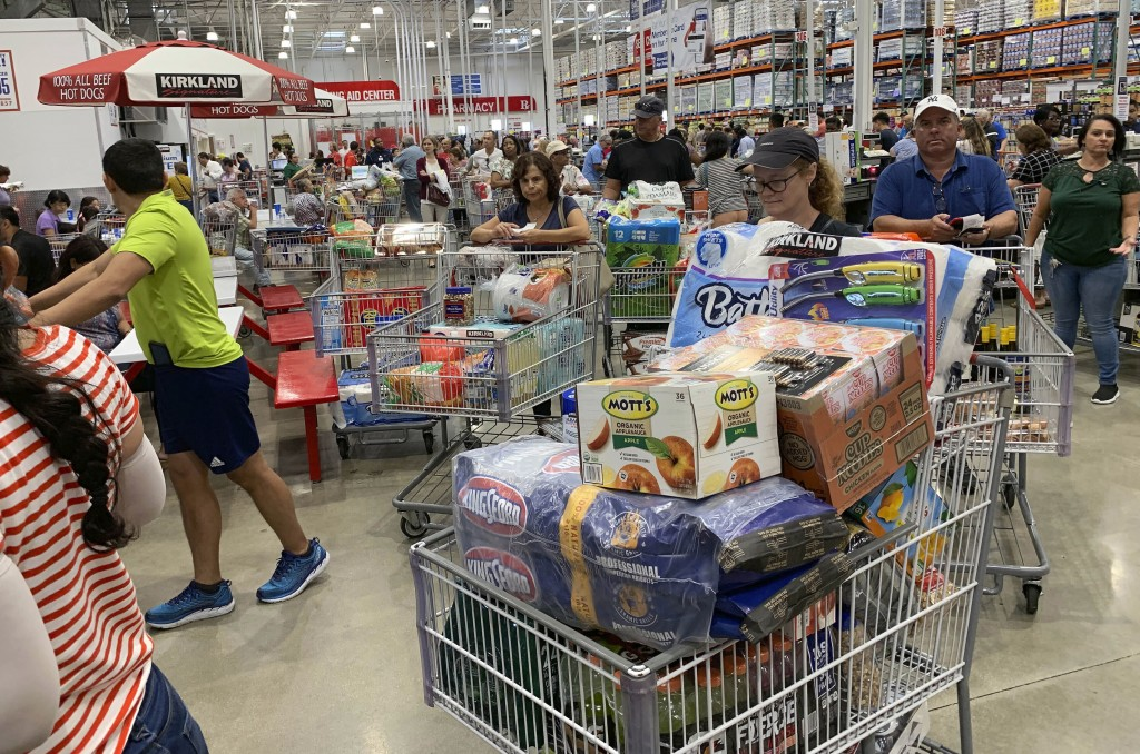 FILE - In this Aug. 29, 2019, photo shoppers wait in long lines at Costco in Davie, Fla. On Thursday, Sept. 12, the Labor Department reports on U.S. c...