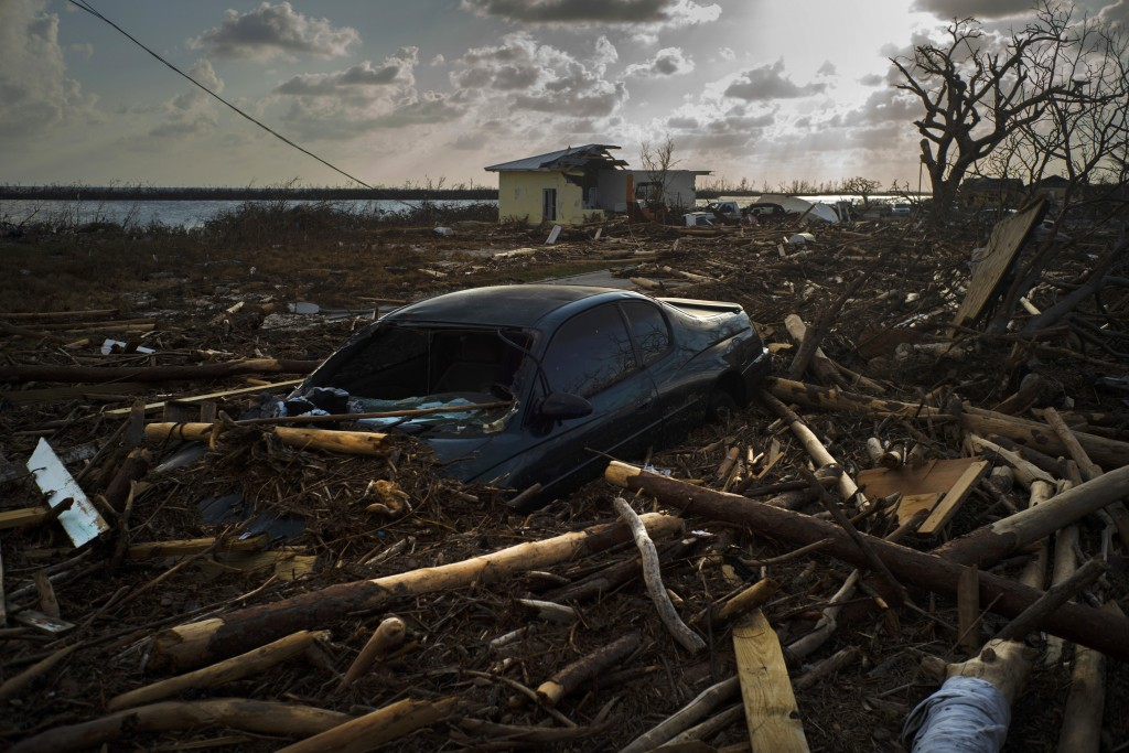 A car is sunk in the wreckage and debris caused by Hurricane Dorian, in Mclean's Town, Grand Bahama, Bahamas, Wednesday Sept. 11, 2019. Bahamians are ...