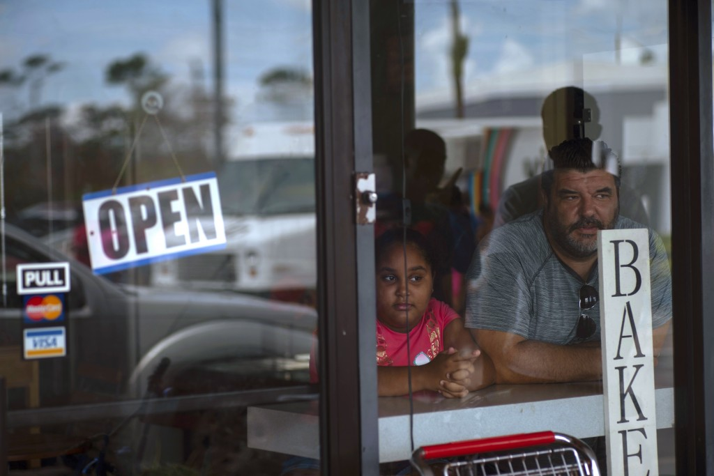 A man and girl peer out from a bakery and cafeteria in Freeport, Bahamas, Wednesday, Sept. 11, 2019. Those who survived Hurricane Dorian are facing th...
