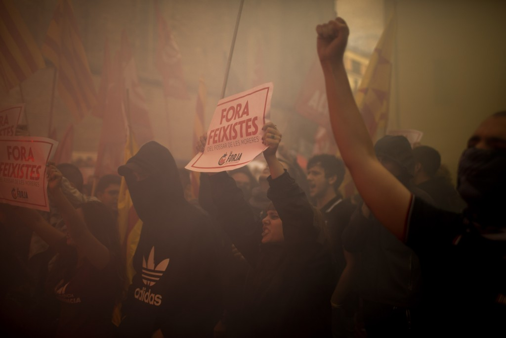 """Demonstrators, one of them holding a banner reading in Catalan """"fascists get out"""", march during the Catalan National Day in Barcelona, Spain, Wednesda"""