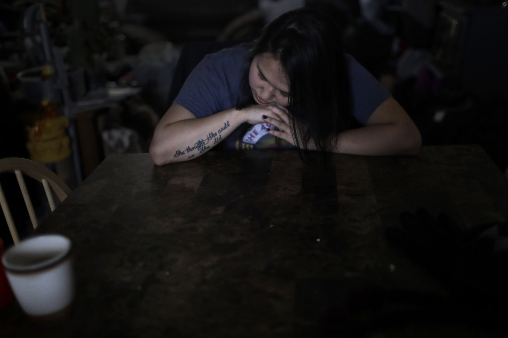 In this Feb. 16, 2019, photo, Deidre Levi rests her head for a moment in her grandmother's house before a basketball game in the Native Village of St....