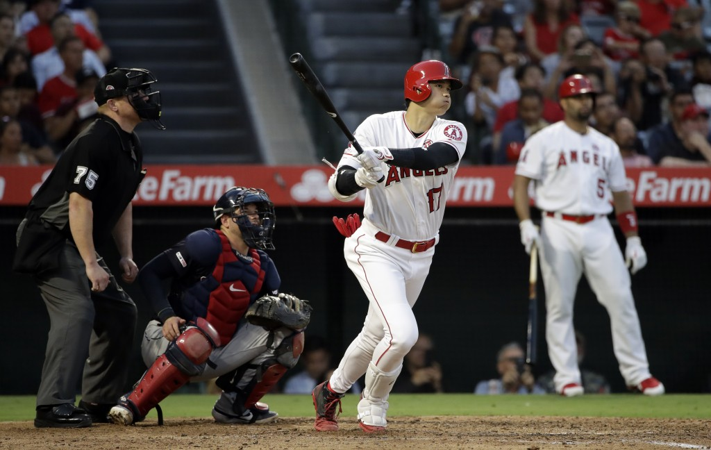 Los Angeles Angels' Shohei Ohtani follows through on a solo home run against the Cleveland Indians during the fifth inning of a baseball game Wednesda...
