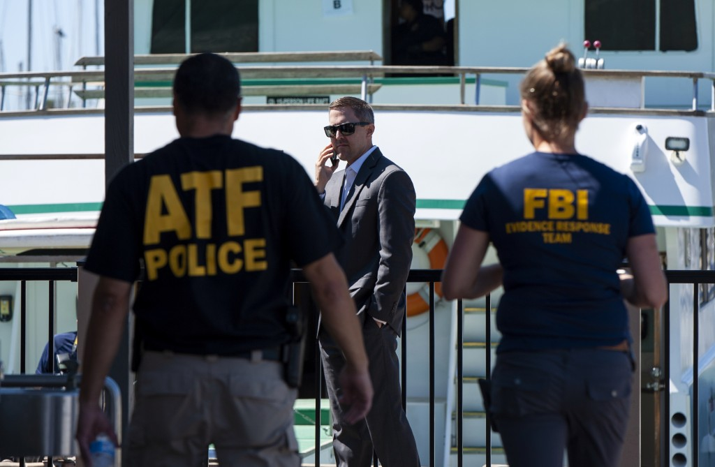 FILE - In this Sept. 8, 2019 file photo, investigators check the Truth Aquatics office on the Santa Barbara Harbor in Santa Barbara, Calif. Authoritie...