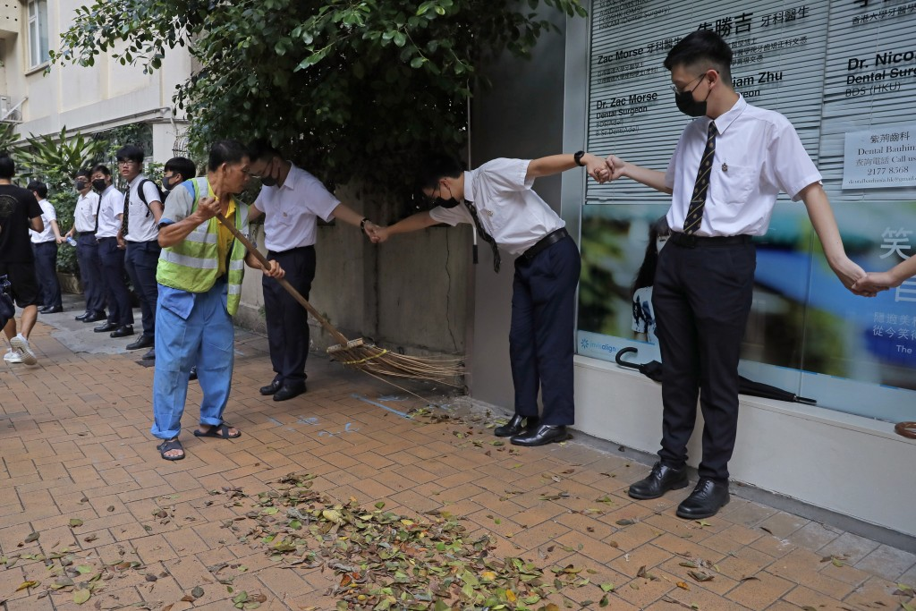A worker sweeps a road as students hold hands to surround St. Paul's College in Hong Kong, Monday, Sept. 9, 2019. Thousands of demonstrators in Hong K