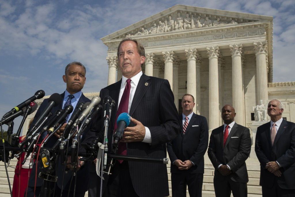 Texas Attorney General Ken Paxton, center, with District of Columbia Attorney General Karl Racine, left, and a bipartisan group of state attorneys gen...