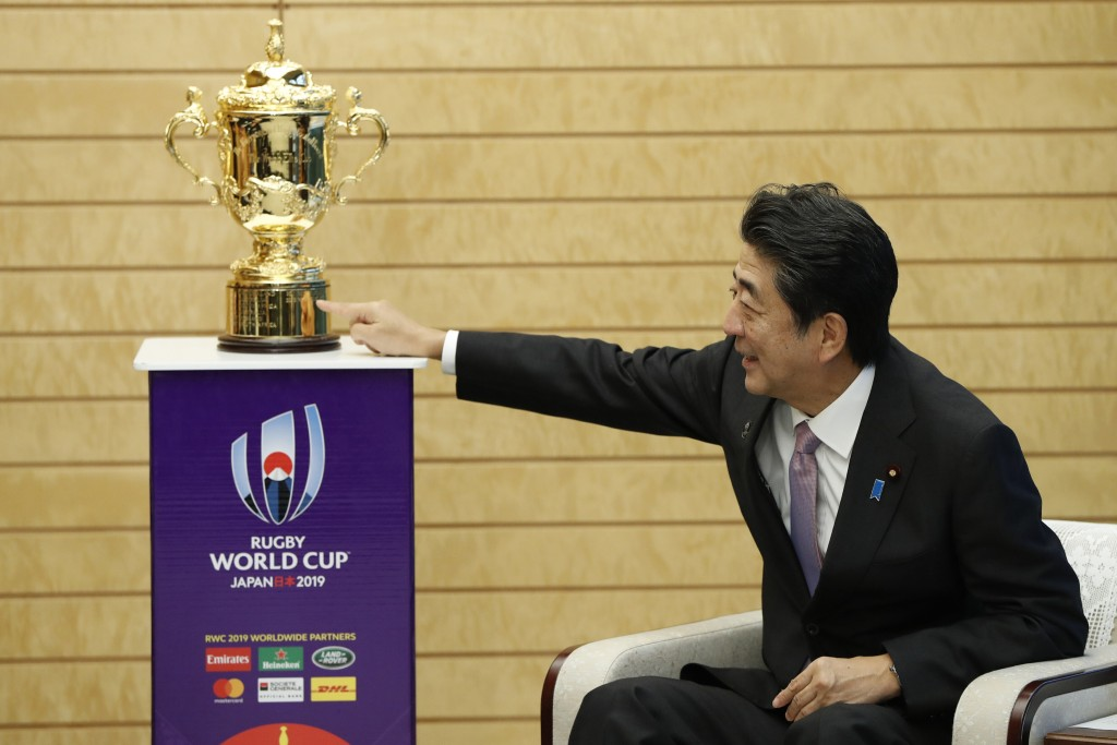 Japan's Prime Minister Shinzo Abe points to the Webb Ellis trophy during a courtesy call by World Rugby officials as part of the trophy tour ahead of