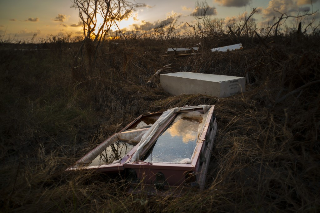 A shattered and water-filled coffin lays exposed to the elements in the aftermath of Hurricane Dorian, at the cemetery in Mclean's Town, Grand Bahama,