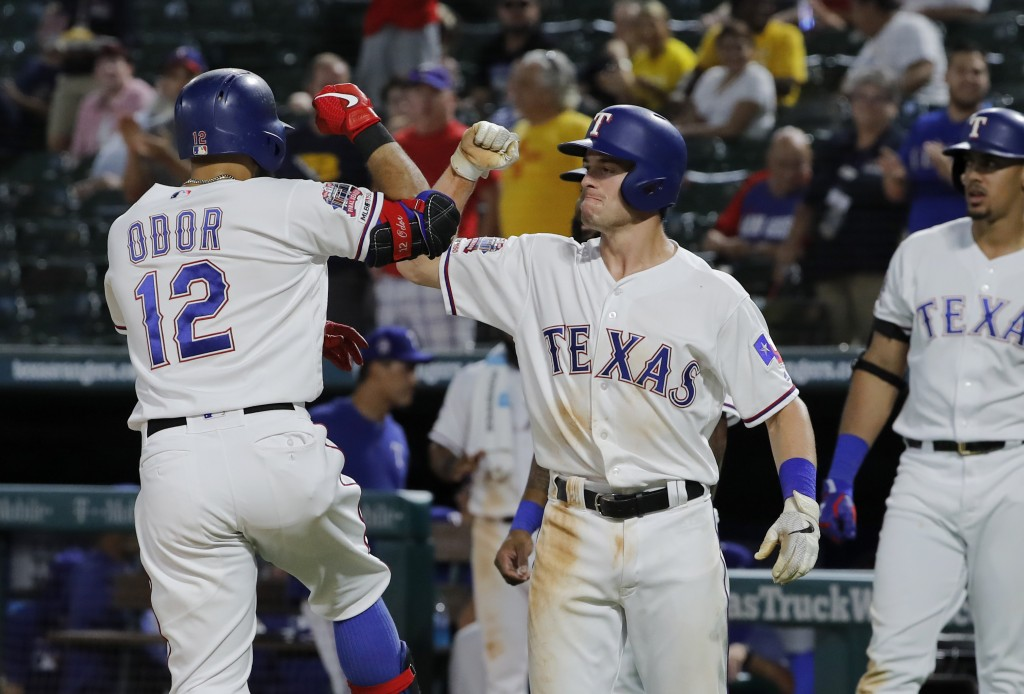 Texas Rangers' Rougned Odor (12) and Nick Solak celebrate Odor's three-run home run as Ronald Guzman, right rear, watches during the seventh inning of