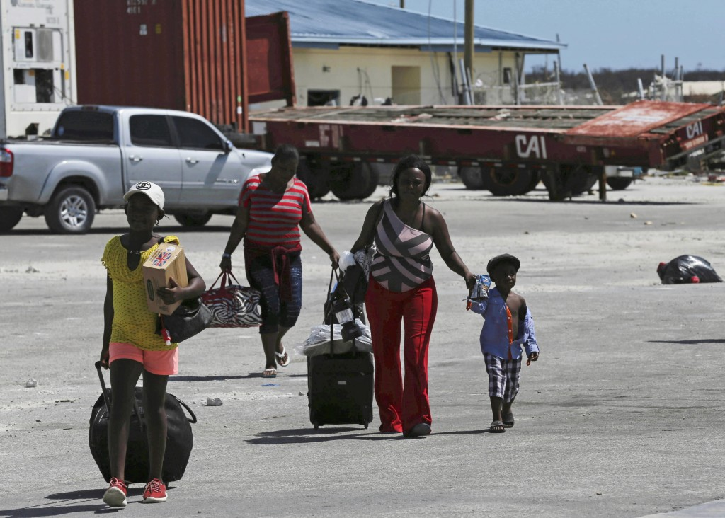 Evacuees carry their belongings as they walk to a ferry to depart for Nassau in the aftermath of Hurricane Dorian, at the port of Marsh Harbor, Abaco ...