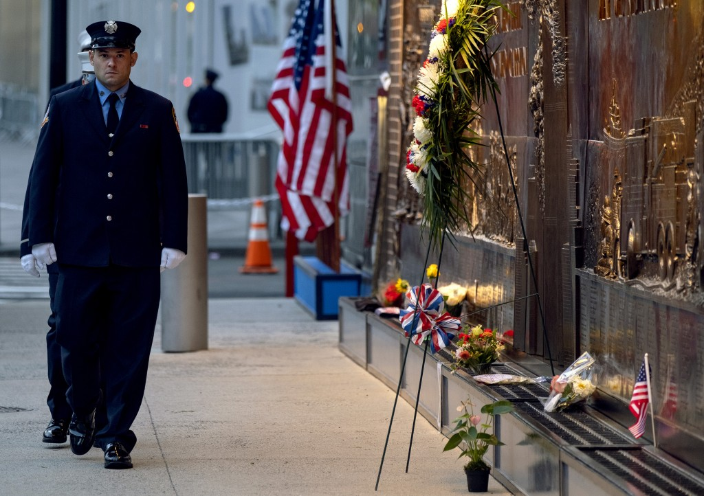 New York City firefighters take a position in front of a memorial on the side of a firehouse adjacent to One World Trade Center and the 9/11 Memorial