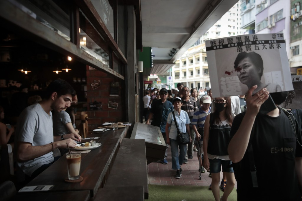 In this Saturday, Aug. 31, 2019, photo, pro-democracy protesters march along a street past a restaurant in Hong Kong. Life is not quite normal after t...