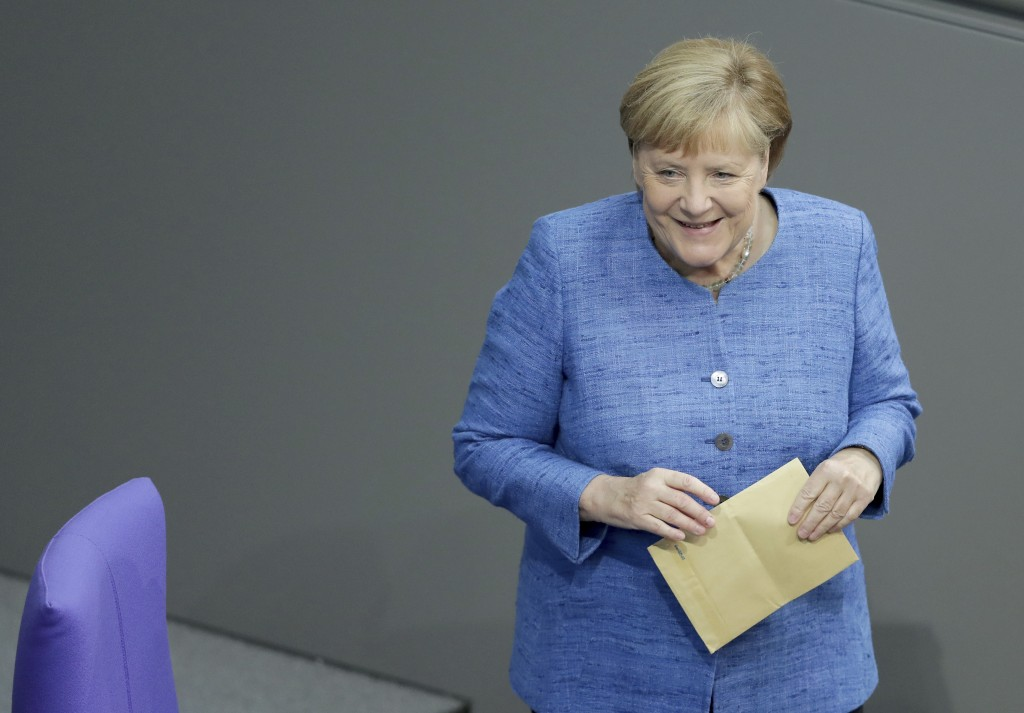 German Chancellor Angela Merkel holds an envelope as she arrives for a meeting of the German federal parliament, Bundestag, at the Reichstag building ...