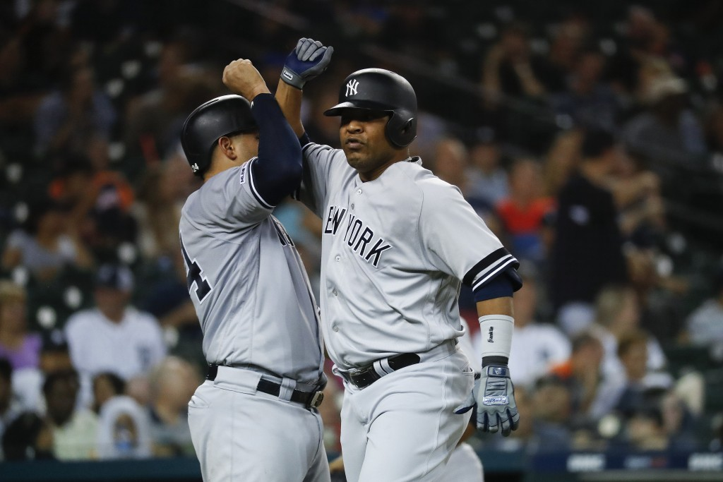New York Yankees' Edwin Encarnacion, right, celebrates his two-run home run with New York Yankees Gary Sanchez in the seventh inning of a baseball gam...