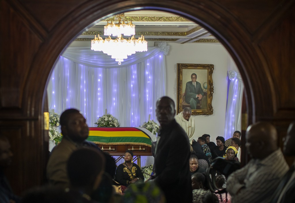 Family members and other mourners gather around the body of former president Robert Mugabe, whose portrait hangs on the wall, as he lies in state insi...