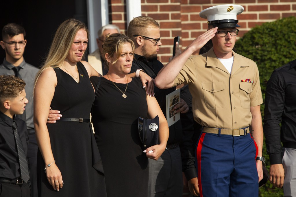 Kiersten Haub, from left, Erika Starke, and Michael Haub, family members of New York firefighter Michael Haub, attend a second funeral service for him...