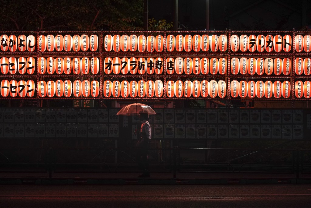 In this Wednesday, Sept. 11, 2019, file photo, a man walks with an umbrella past lanterns in the Nakano district of Tokyo. (AP Photo/Jae C. Hong, File