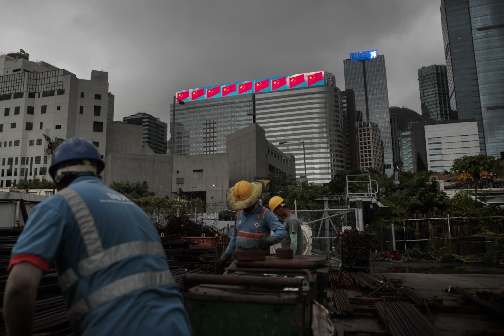 In this Sept. 2, 2019, photo, workers bundle rebars at a metal yard as a building displaying Chinese national flags is seen in the distance in Hong Ko...