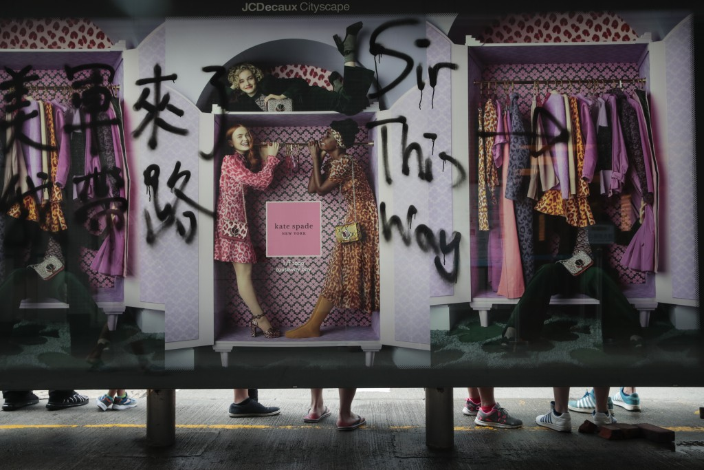 In this Sept. 1, 2019, photo, people wait for buses at a bus stop vandalized by protesters in Hong Kong. Life is not quite normal after three months o...