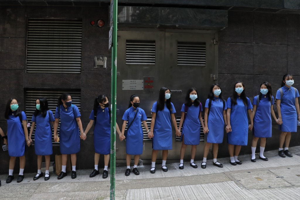 Students wearing mask hold hands to surround St. Stephen's Girls' College in Hong Kong, Monday, Sept. 9, 2019. Thousands of demonstrators in Hong Kong