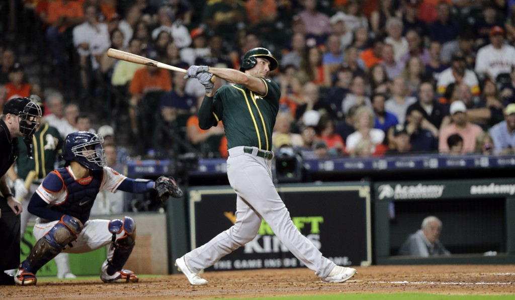 Oakland Athletics' Matt Olson, right, hits a two-run home run as Houston Astros catcher Robinson Chirinos reaches for the pitch during the third innin...