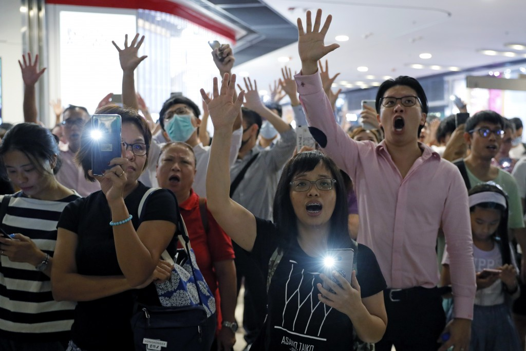 """Demonstrators sing a theme song written by protestors """"Glory to Hong Kong"""" at the International Finance Centre (ifc) shopping mall in Hong Kong, Thurs..."""
