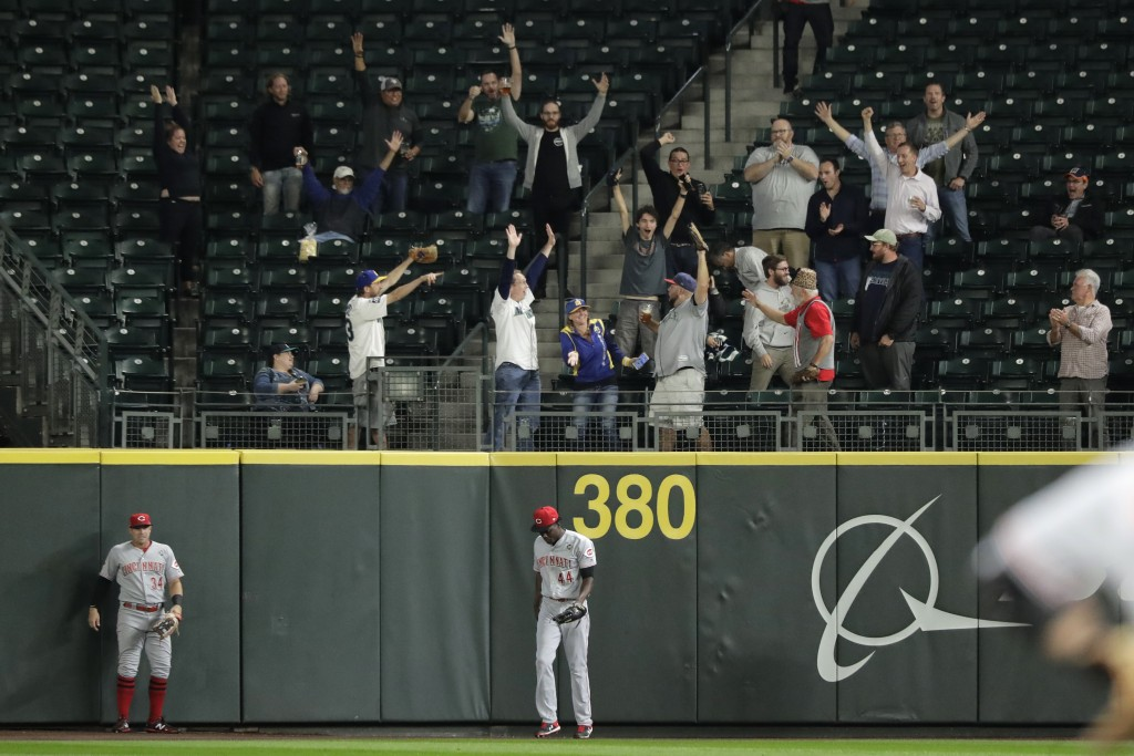 Cincinnati Reds right fielder Aristides Aquino (44) stands at the wall as fans celebrate after Seattle Mariners' Kyle Lewis hit a three-run home run d