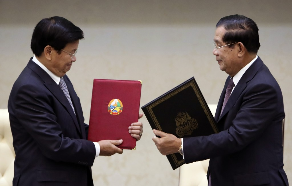Cambodian Prime Minister Hun Sen, right, exchanges a document letter with his Laos counterpart Thonloun Sisoulith, during a signing ceremony, in Phnom