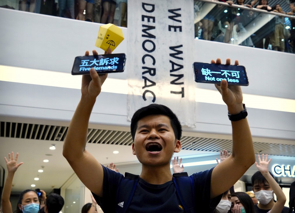 """A demonstrator holds up cell phones reading """"Five demands - not one less"""" during a demonstration at the Times Square shopping mall in Hong Kong, Thurs..."""