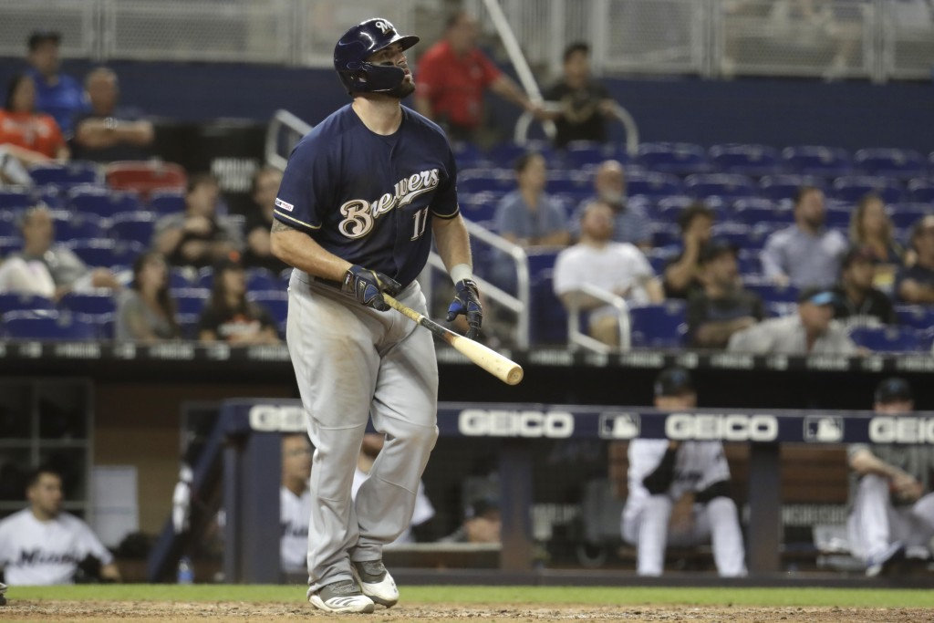 Milwaukee Brewers' Mike Moustakas (11) watches after hitting a two run home run during the ninth inning of a baseball game against the Miami Marlins, ...