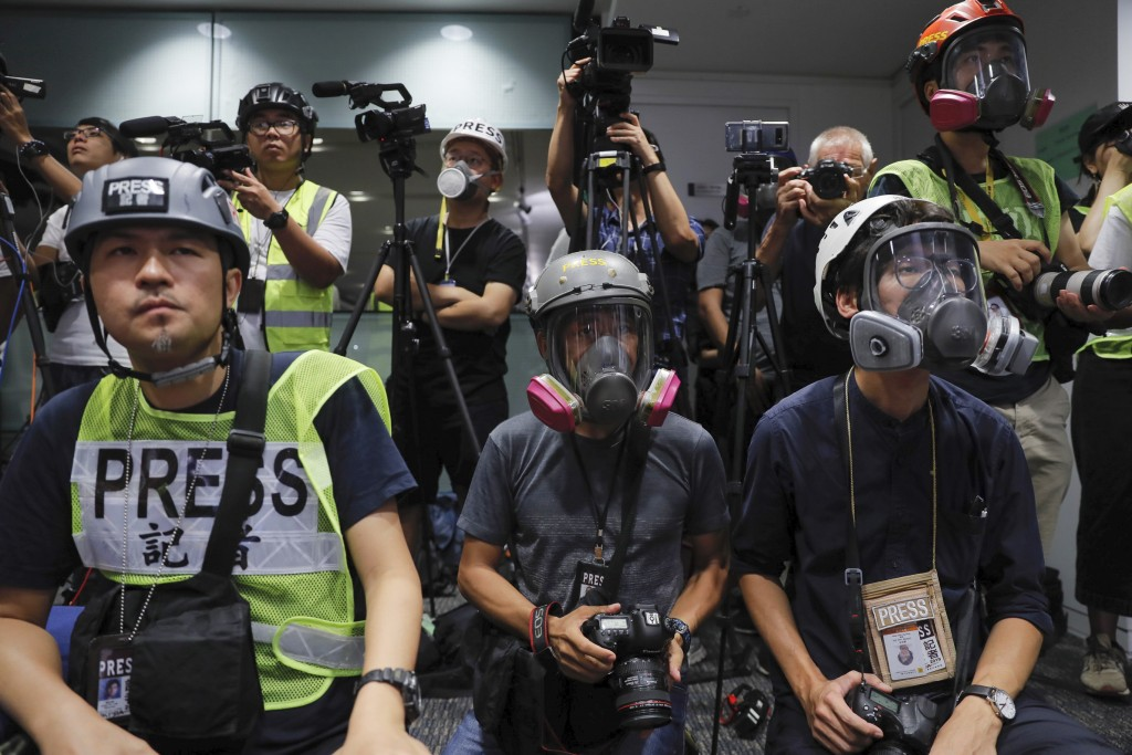 In a sign of protest against the police using force against the media, press photographers wear protective gear during a police media conference in Ho...