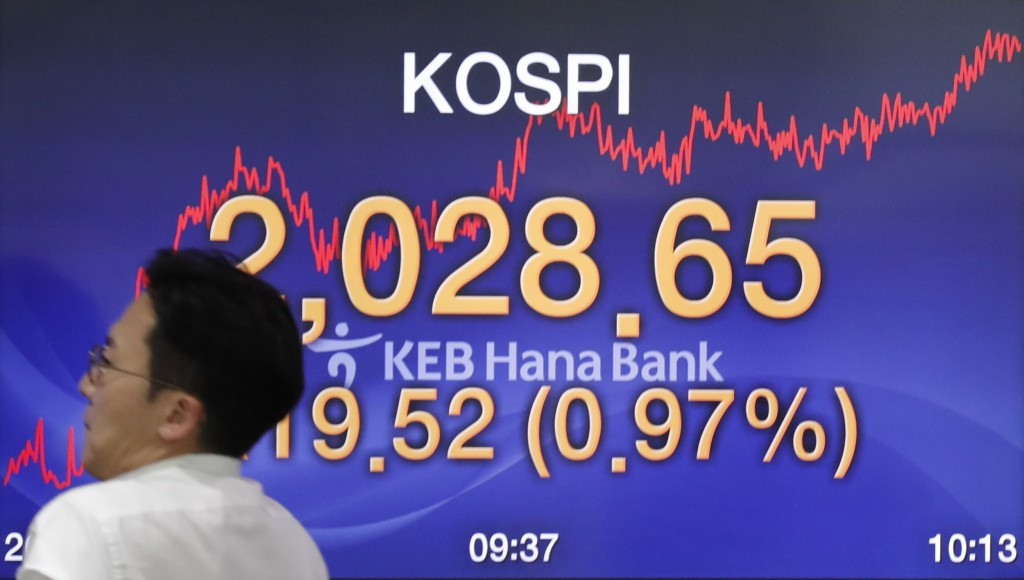 A currency trader walks by the screen showing the Korea Composite Stock Price Index (KOSPI) at the foreign exchange dealing room in Seoul, South Korea