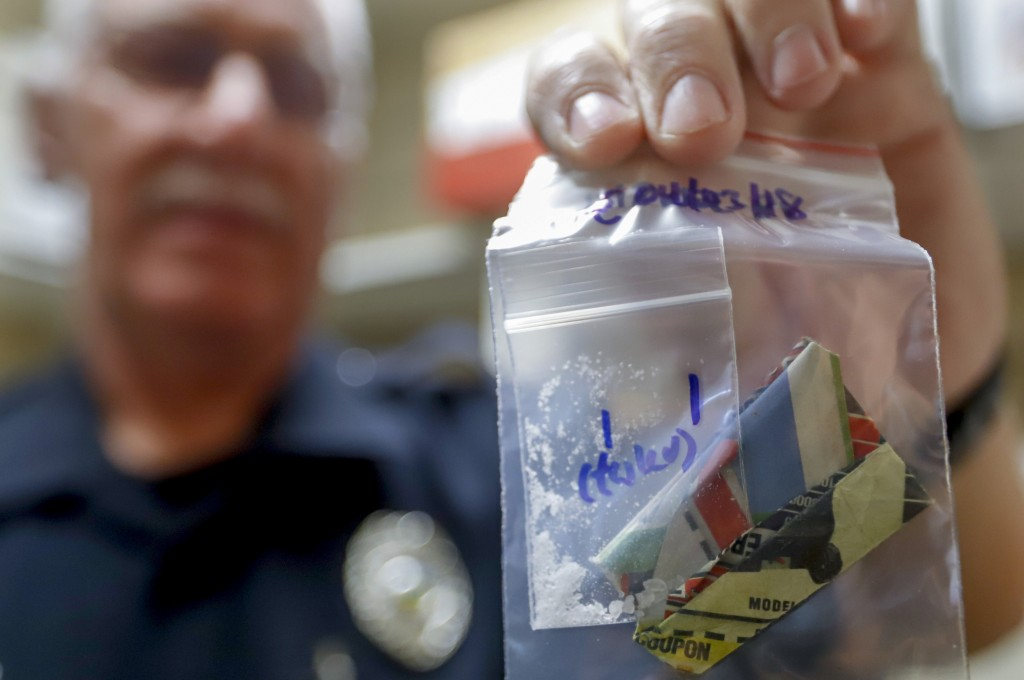 In this Sept. 11, 2019, photo, narcotics detective Will Pfeiffer shows a stored evidence bag that containing methamphetamine before it is destroyed in