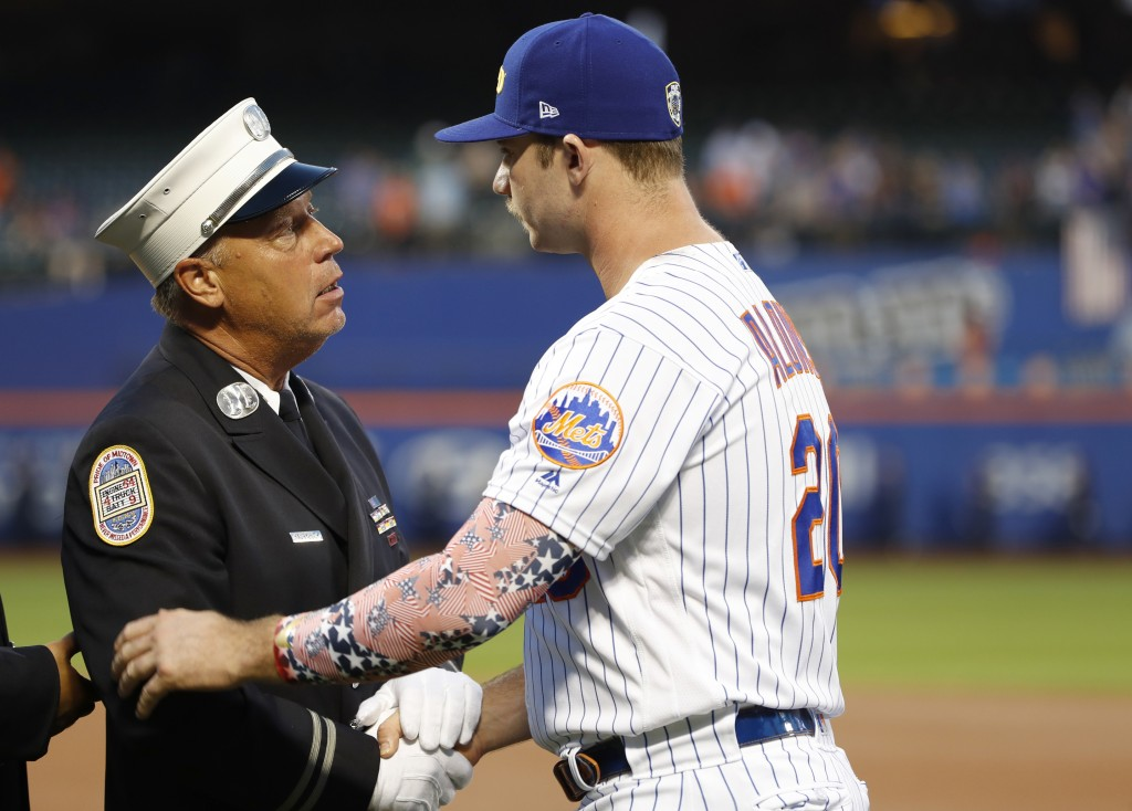 A member of the New York City Fire Department greets New York Mets' Pete Alonso during a Sept. 11, 2001, tribute before the team's baseball game again