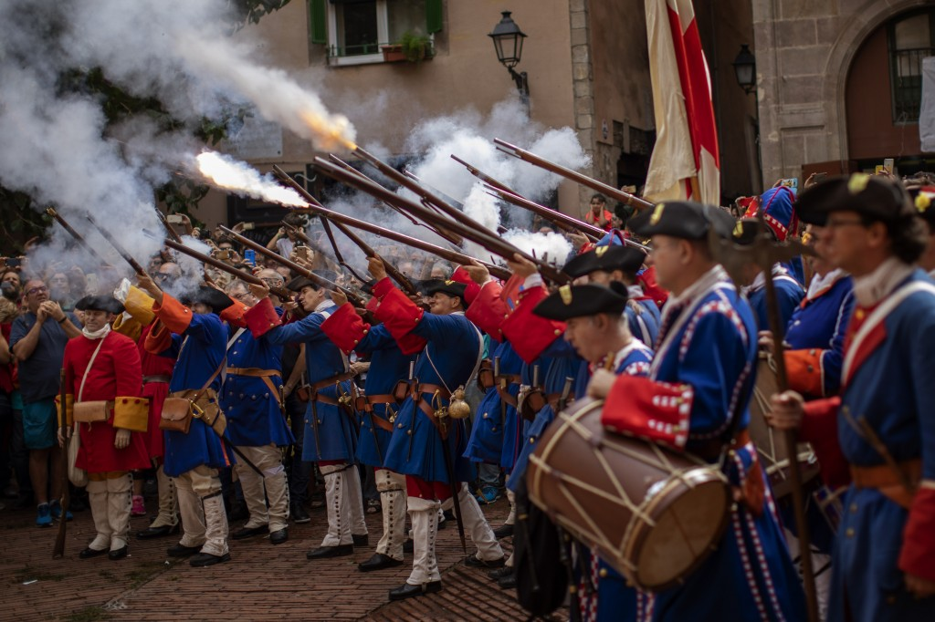 Men dressed in costume shoot their rifles during a performance to celebrate the Catalan National Day in Barcelona, Spain, Wednesday, Sept. 11, 2019. T...