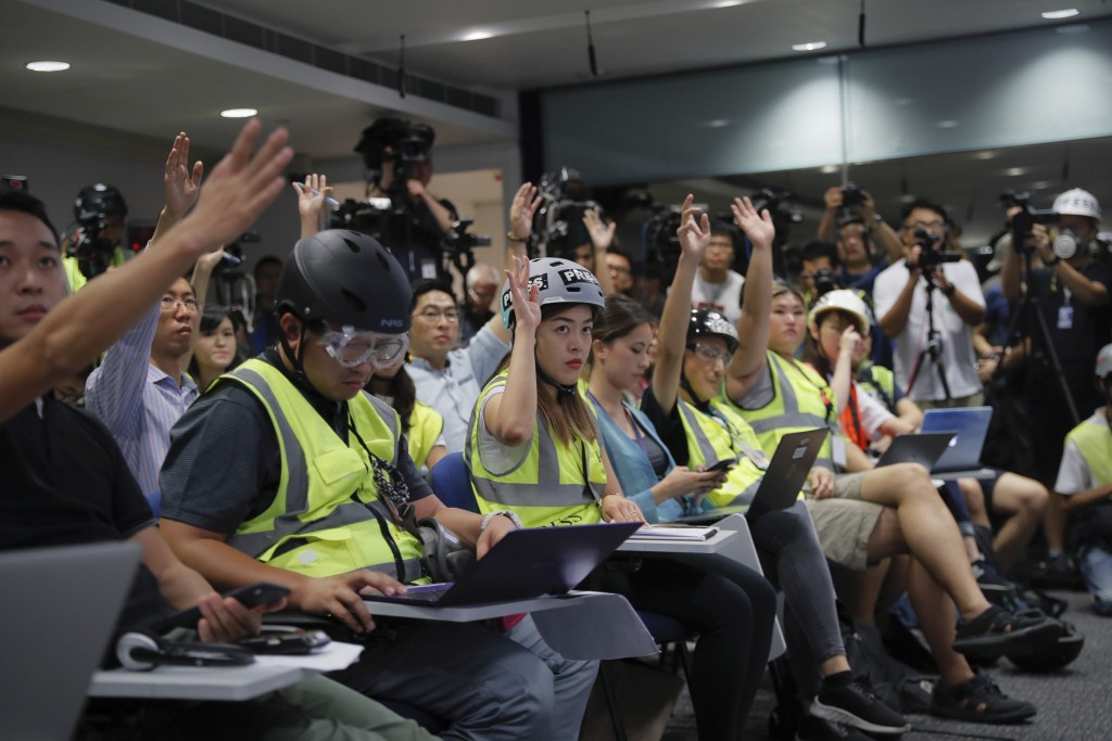 In a sign of protest against the police using force against the media, journalists wear protective gear during a police media conference in Hong Kong,...
