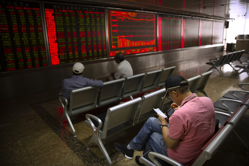 A Chinese investor uses his smartphone as he monitors stock prices at a brokerage house in Beijing, Wednesday, Sept. 11, 2019. Asian shares were mostl...